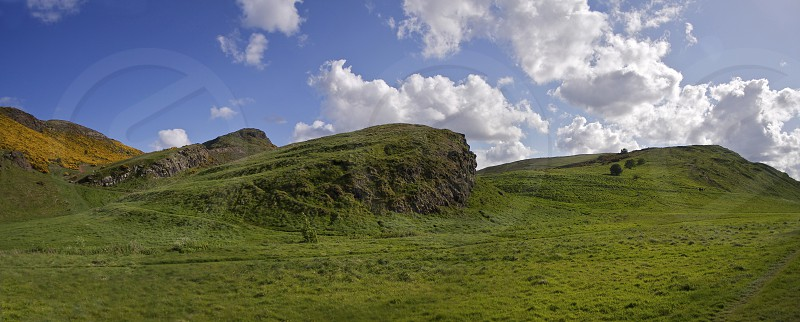 Bright green grass covering the hills and crags of Edinburgh's Arthur's seat.  Blue skies with bright white clouds. photo