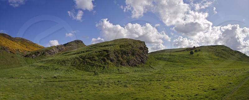 Arthur's Seat Edinburgh Scotland.  Green grass blue sky blue skies landscape scenic clouds cumulus panoramic photo