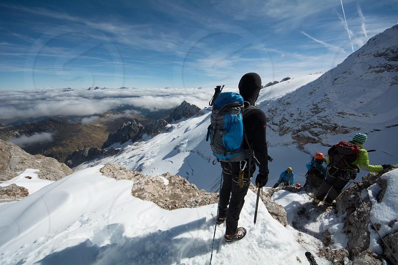 Standing man waiting to climb down from highest peak of Italian Dolomites - Marmolada photo