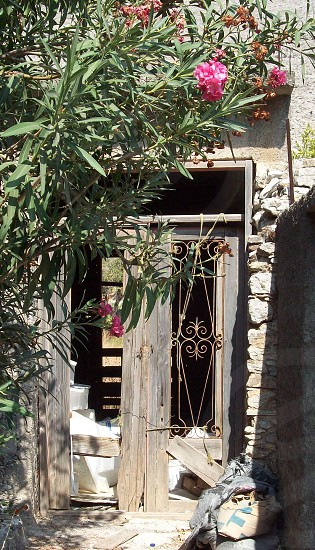 Oleander - door - rotten 0 wooden 0 erosion - decaying - window box - ventilation - restoration -  just a lick of paint - holiday home - home in the sun - time share - dream home - desirable residence - Greek architecture - Greek Door - Greece - shabby - needs TLC photo