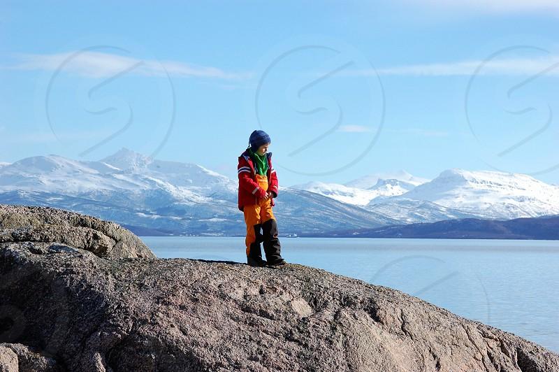 man standing in big rock photo
