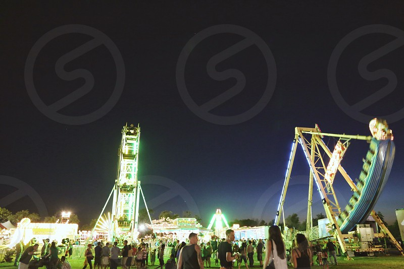 people standing beside rides during nighttime photo