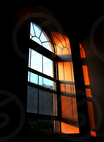 Light comes through an arched window and it s window panes and shadows  play on the inside wall.   photo