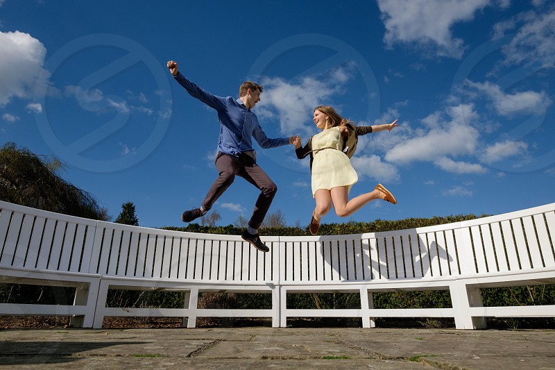 young couple jumping off a white long wooden garden bench in the sunshine looking at each other he is wearing a blue shirt and great trousers and she is wearing a yellow dress with a brown cardigan photo