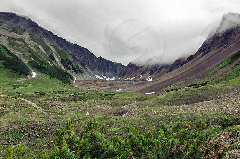 Summer mountain landscape of Kamchatka: beautiful view of mountain circus with rocky slopes in cloudy weather. Eurasia Russian Far East Kamchatka Peninsula Mountain Range Vachkazhets. photo