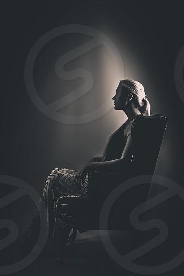 Model sitting in dimly lit chair portrait  photo