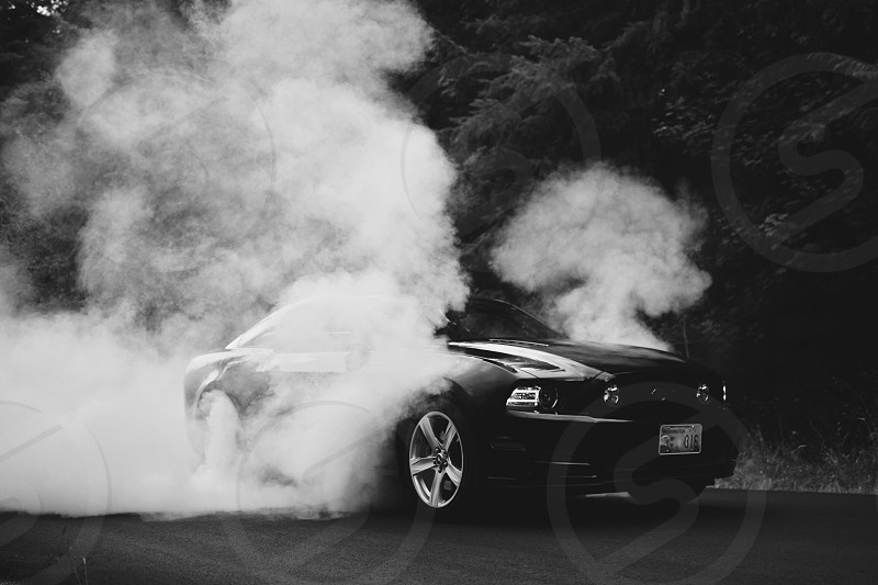 grayscale photo of ford mustang doing burn out photo