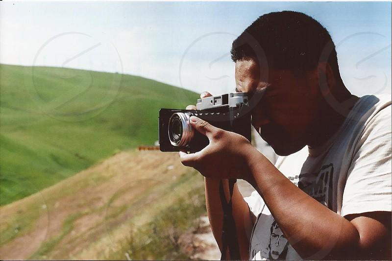 man wearing white shirt taking a photograph photo