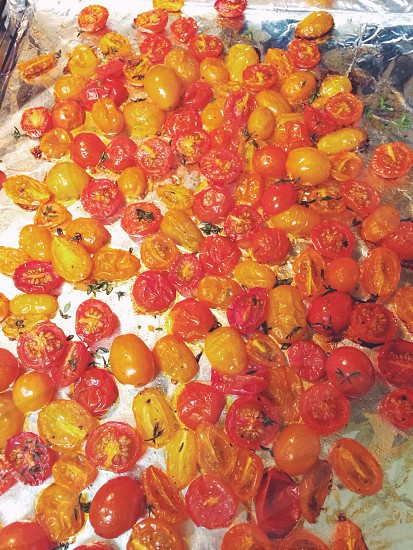 Roasted multicolor grape tomatoes with rosemary and thyme and olive oil on a baking sheet/roasting pan hot out of the oven.  photo