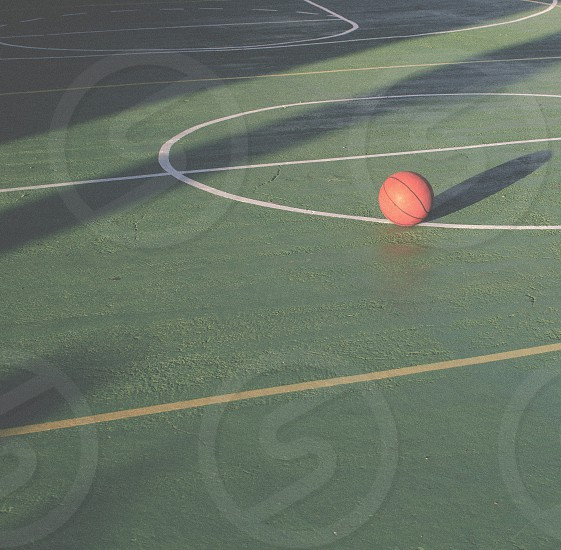 a basketball ball on a deserted green court at the afternoom photo