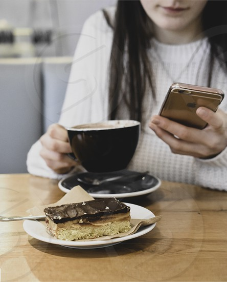 Girl drinking hot chocolate and eating chocolate cake in a cafe. photo