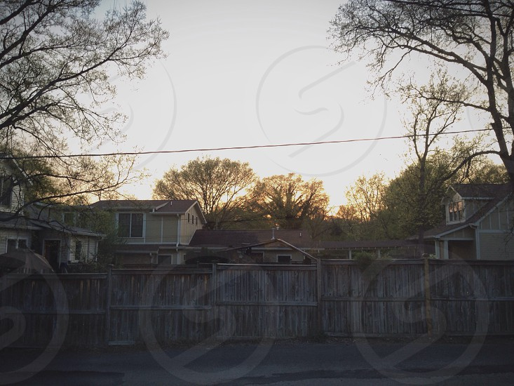 brown wooden fence beside house during daytime surrounded by trees photo