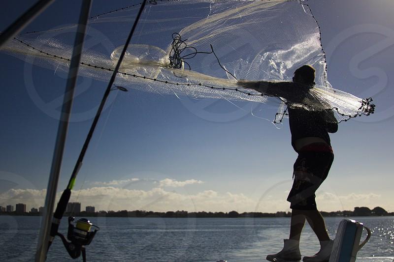 man fixing the fish net photo