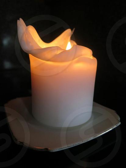 White candle burning on white plate black background photo
