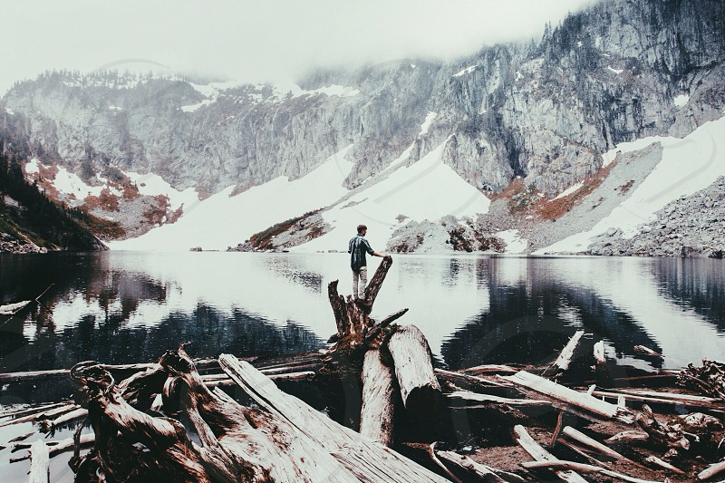 view of man by lake and snowy mountain photo