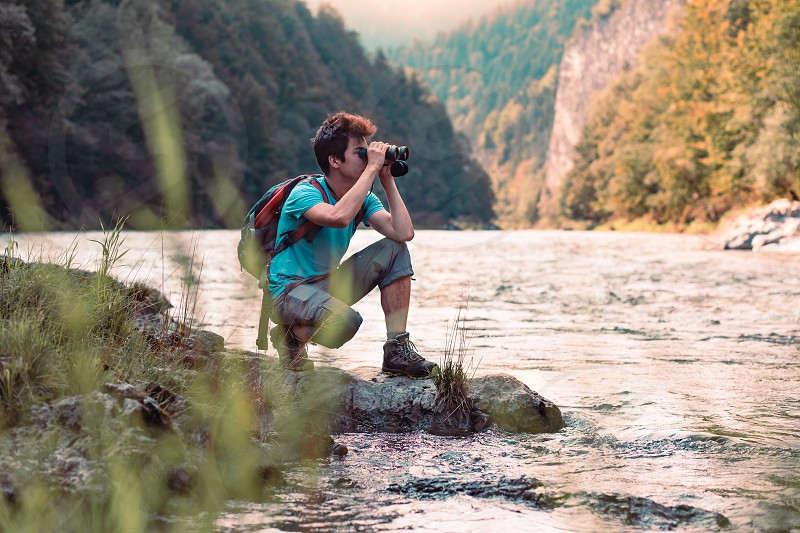 Young tourist with backpack looks through a binoculars on mountains peaks stands on a rock over a river. Boy spends a vacation in mountains wandering with backpack he is wearing sports summer clothes photo