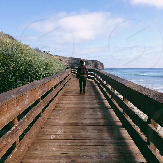 person wearing brown plaid shirt walking down brown wood walkway with guardrail overlooking ocean photo