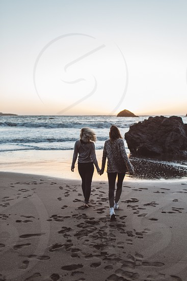 two people holding hands on the beach photo