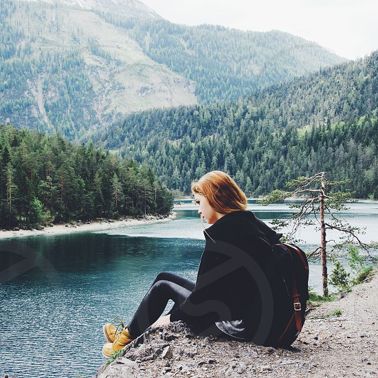 woman in black with daypack sitting by the river photo