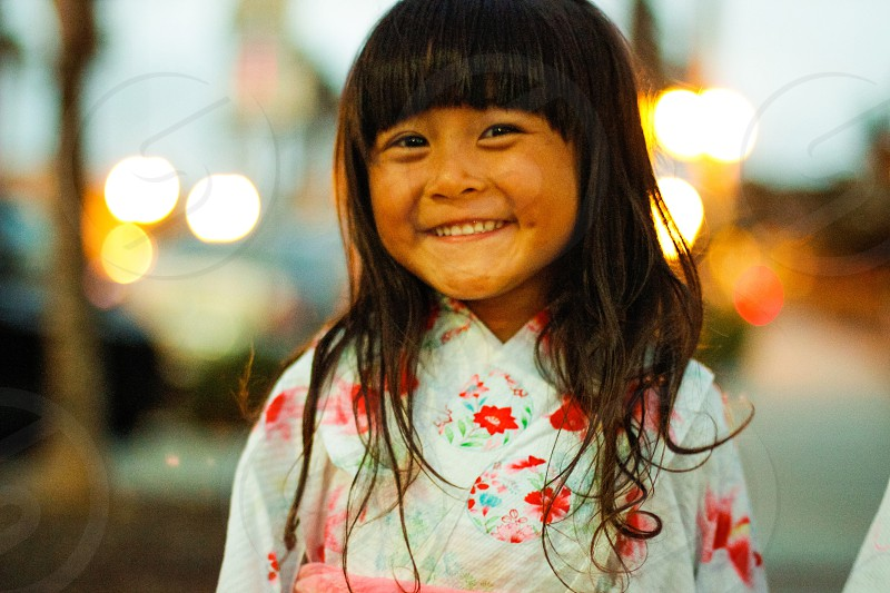 close up photography of girl in white and red floral long sleeve dress smiling photo