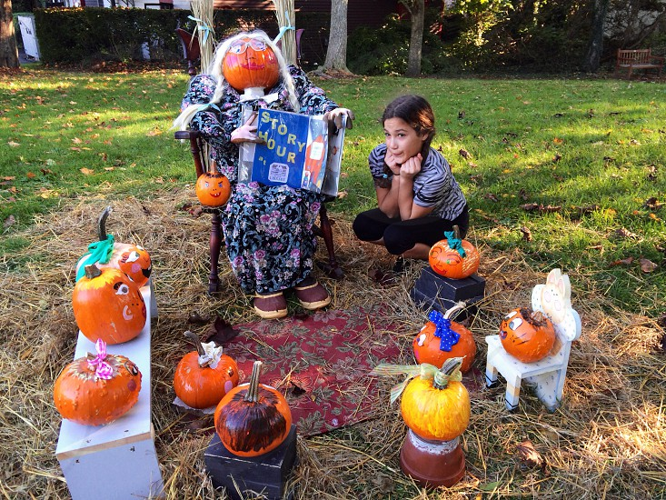 girl sitting with decorated pumpkins and scare crow having story time photo