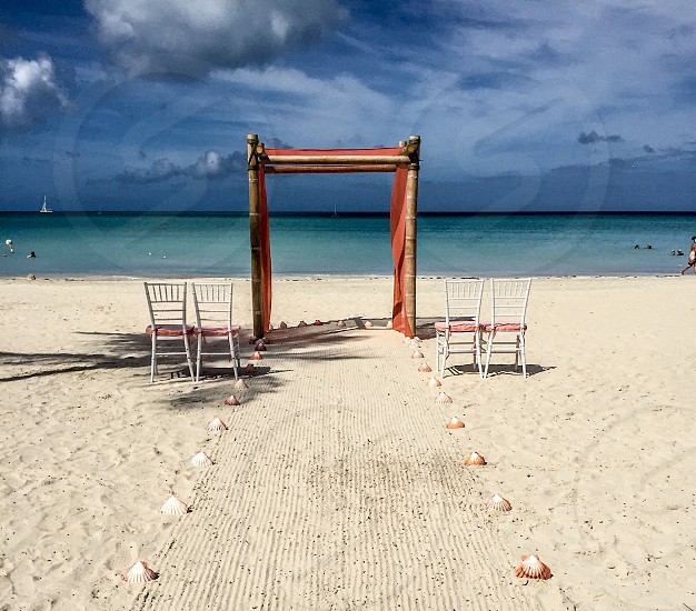 brown bamboo arc with red curtain on white sand beach wedding venue near body of water photo