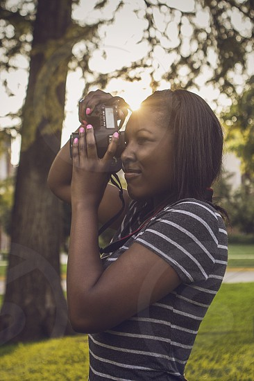 A young girl takes a photograph with a DSLR.  photo