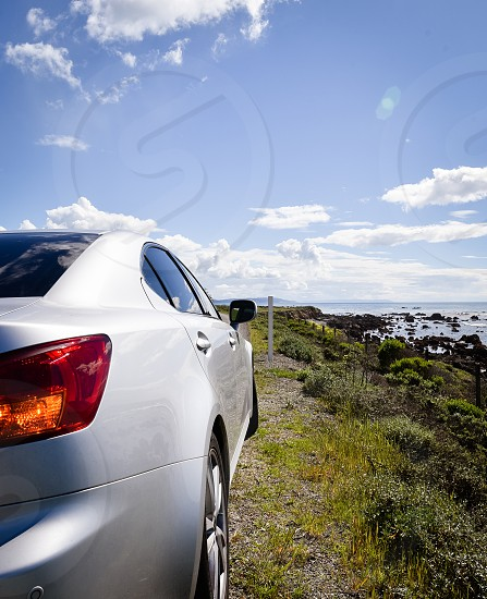 grey car on gray hill with green grass under blue sky with white clouds photo