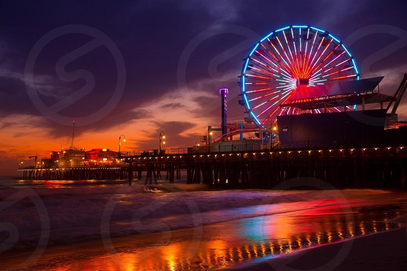 Santa Monica California sunset on Pier Ferrys wheel and reflection on beach wet sand photo