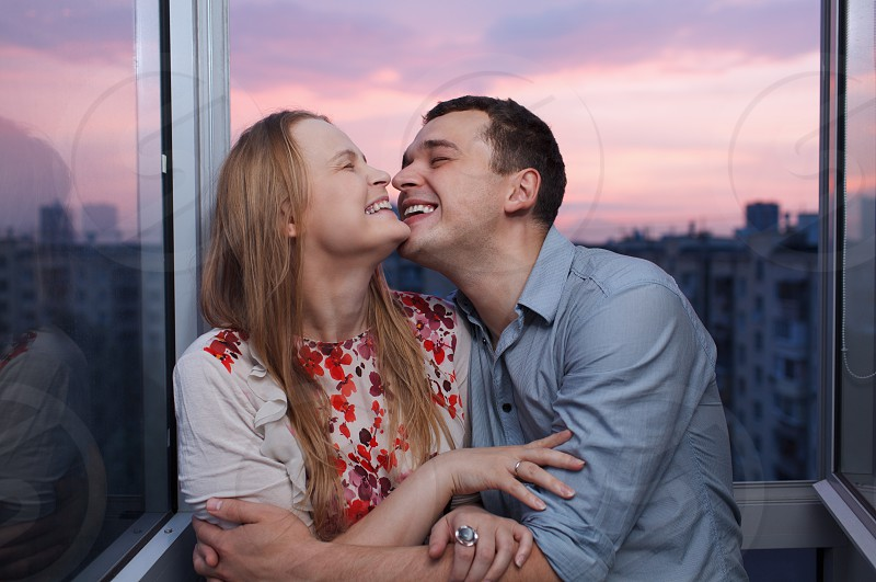 Playful young couple embracing and laughing on the balcony at a high floor during sunset photo