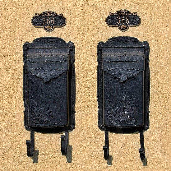 twin retro metal mailboxes are attached to a yellow wall. photo