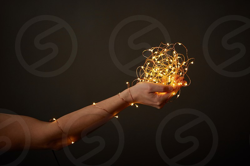 A girl's hand holds a bunch of bright garlands around a dark background with copy space. Christmas celebration photo