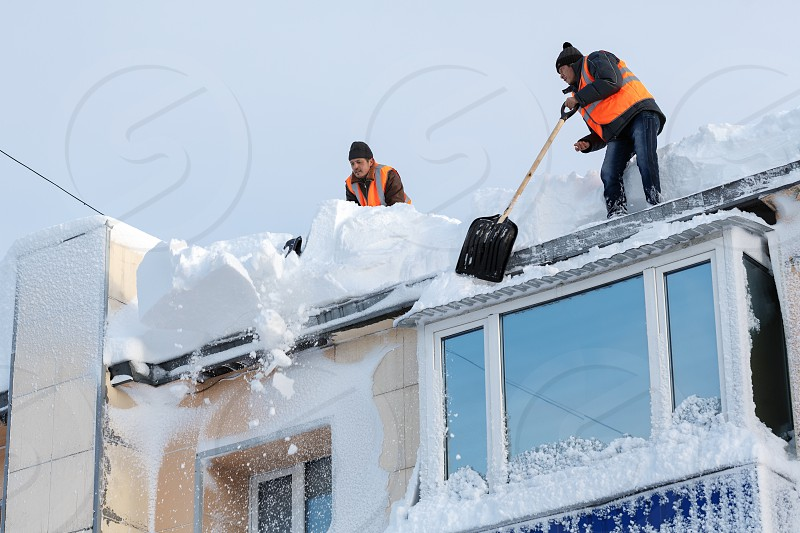 PETROPAVLOVSK CITY KAMCHATKA PENINSULA RUSSIA - DEC 27 2017: Workers in orange vests with snow shovels cleaning snow drifts from roof of multistory building after bad weather (snowstorms blizzard) photo