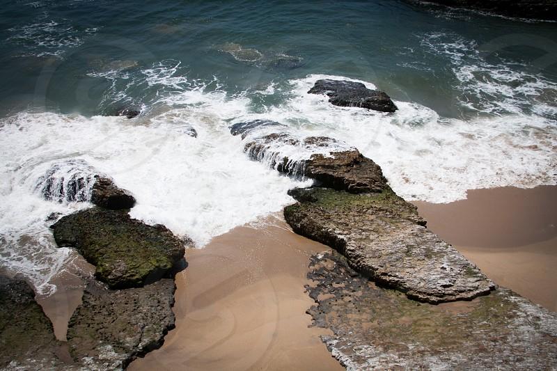 Waves crashing over rocks on a beach photo