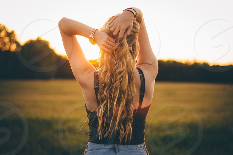 woman in black tank top and blue denim bottoms holding her hair back during sunrise photo