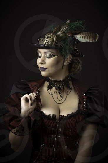Emotional Portrait of Young Woman in Steampunk or Retro style. Studio shot. Model on a Black Background photo