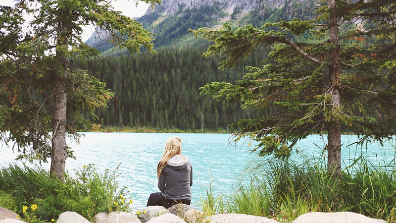 woman sitting on stone watching blue water photo