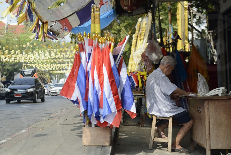 a shop with thai falgs and a pictures of the King Bhumibol near the democracy monument in Banglamphu in the city of Bangkok in Thailand in Southeastasia. photo