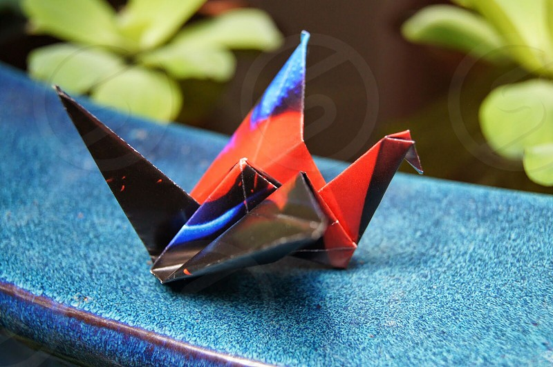 red blue and black origami on blue textile photo