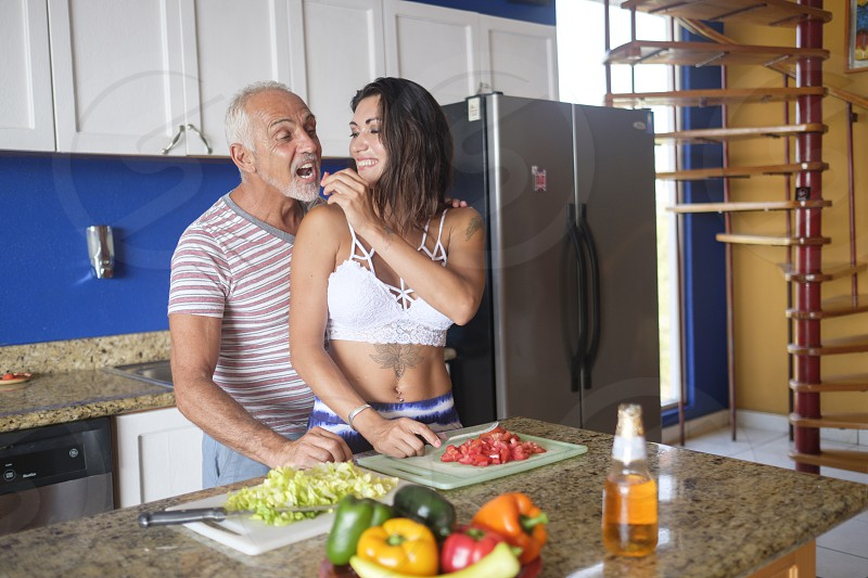 Young woman and older man enjoying to cut vegetables and feeding each other in their apartment kitchen photo