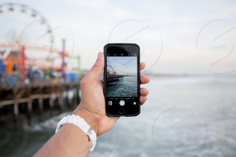 person holding space grey iphone 6 standing taking a picture to the ferries wheel photo