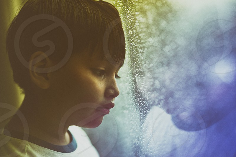 close up portrait of young boy sad mood by the window during raining photo