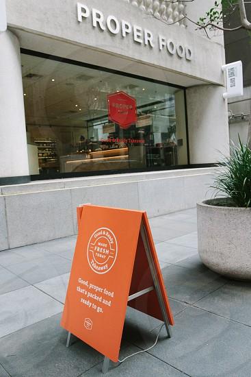 orange wooden signage beside proper food store photo