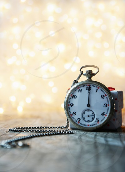 Vintage clock showing midnight with blur lights in the background photo
