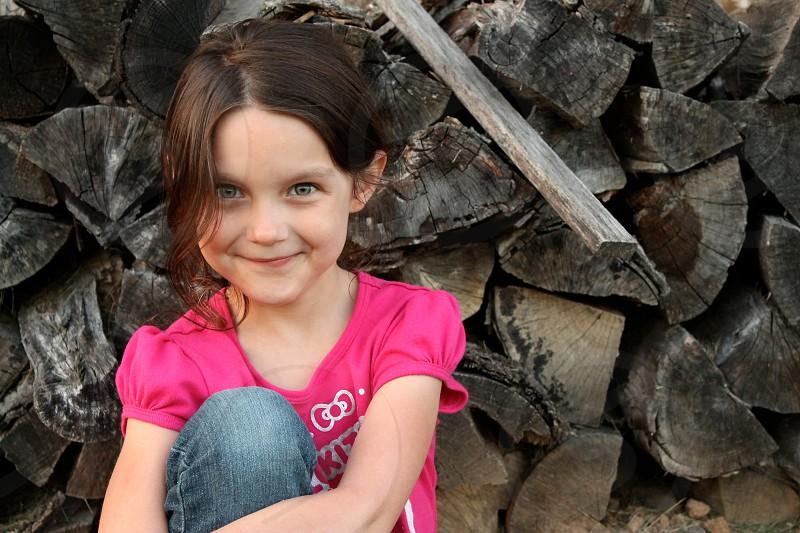 Child outside.  Woodpile. photo