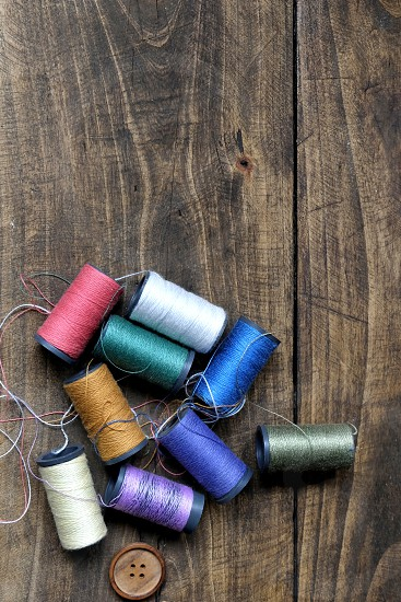 Sewing thread  or bobbins on a old rustic wooden table photo