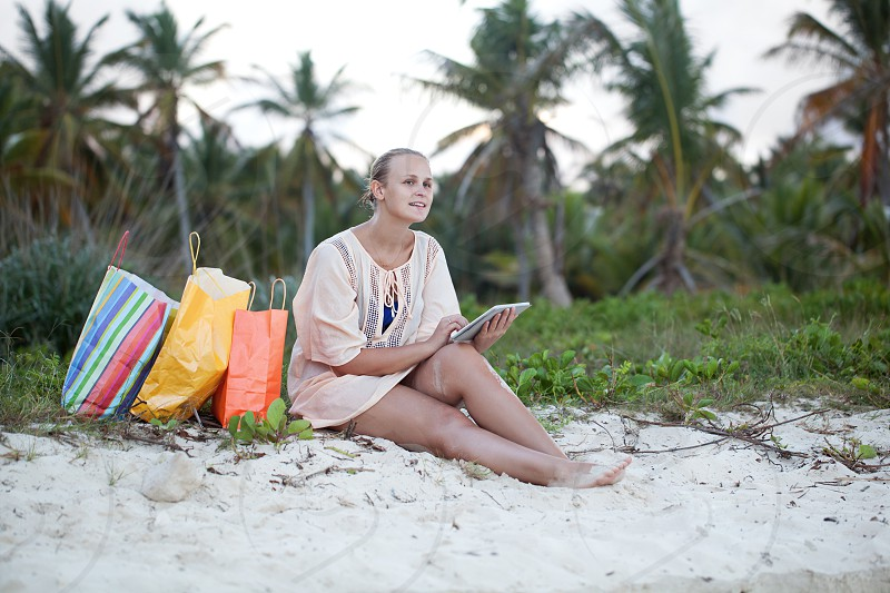 Young smiling woman using tablet computer sitting on the beach after good shopping. Leisure during summer vacation photo