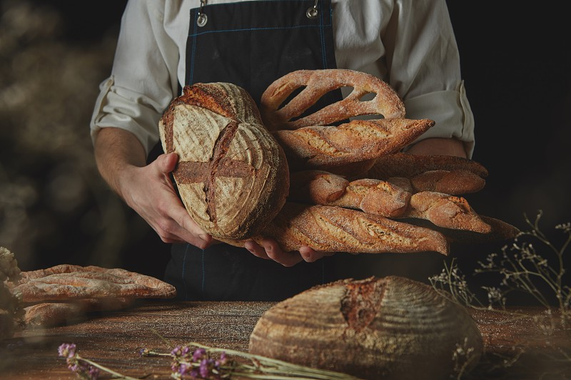 Men's hands hold a variety of bread on the black background of a wooden table with dry flowers photo
