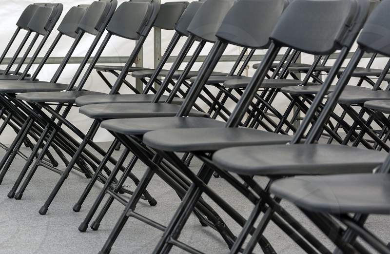 numerous folding chairs arranged in a row in a conference room. photo