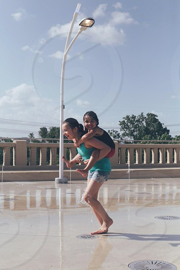 two children smiling standing outdoors photo
